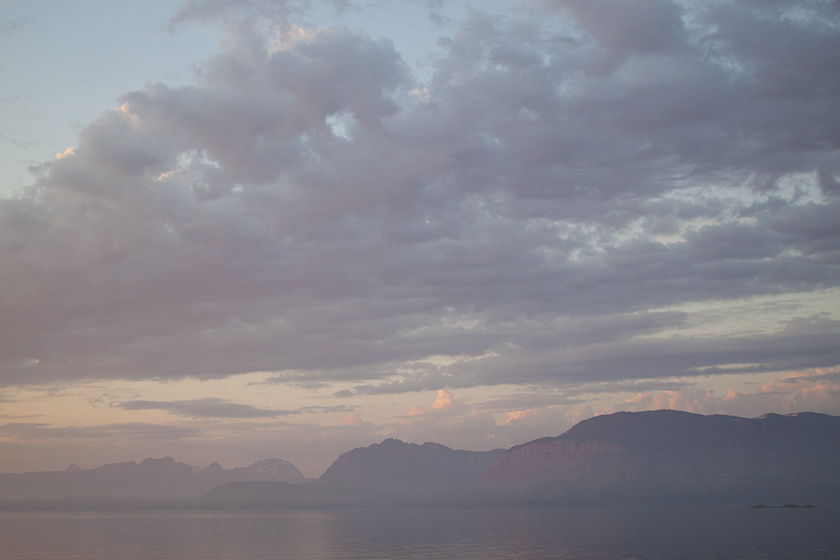 A landscape at sunset, with cloudy skies, faraway mountains, and a sliver of calm ocean. Everything is in soft, pastel colours.