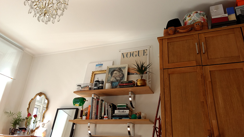 The view from my bed, showing a room with high ceilings and white walls. There is a tall wardrobe with shoe boxes on top, two shelves filled with artwork and books, and an ornate mirror and some plants.