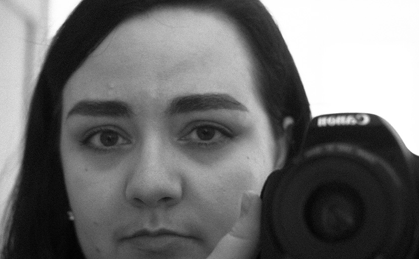 A grainy, black and white photo of Maria. She's a white woman with dark hair and dark eyes. She's holding a camera up by her face, taking the picture in a mirror.