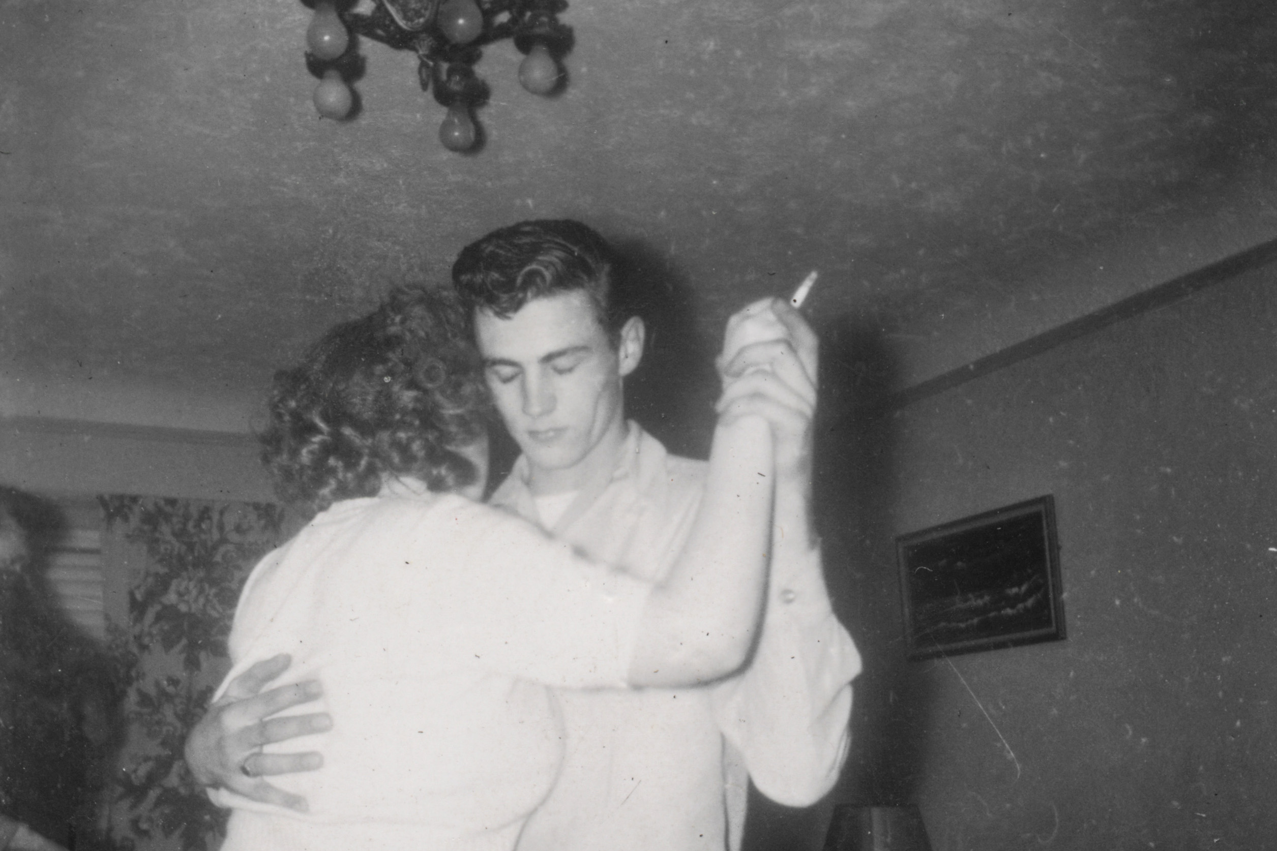 A vintage black-and-white photo of two people dancing. The man has a fifties hairstyle, and has his eyes closed. The person he is dancing with has curled hair, and is holding a cigarette between their clasped hands.